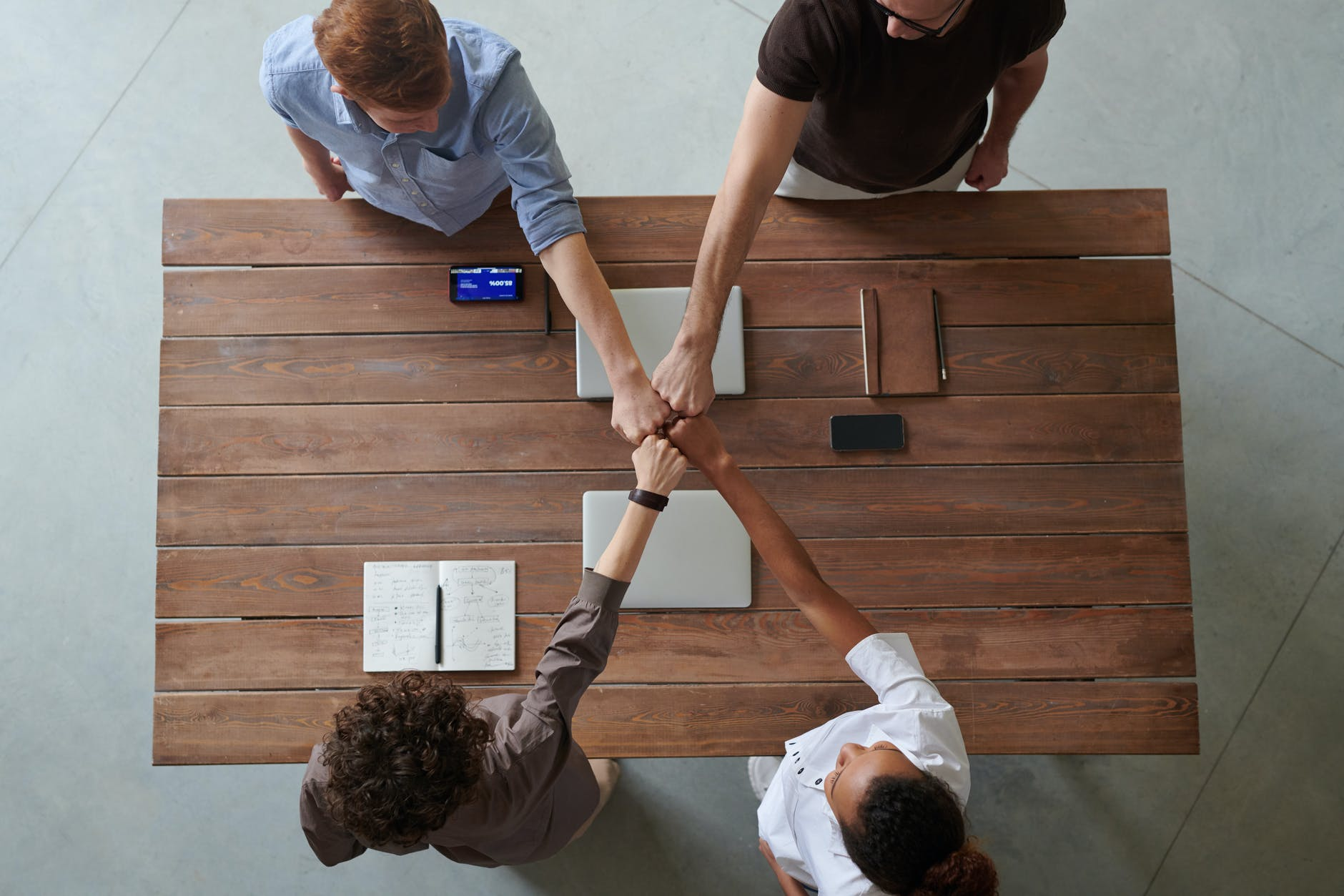 Group of people around a brown wooden rectangle table flanked each side by two people all joining their hands in a fists in the middle of a table.
