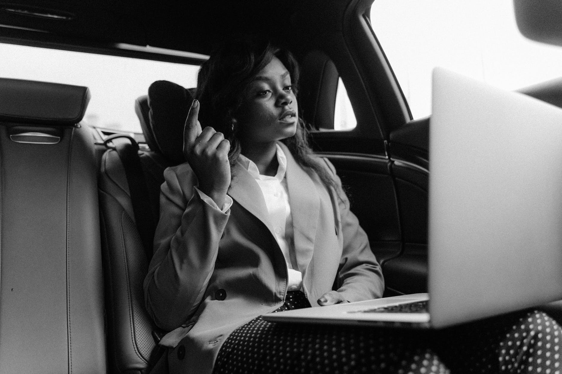 A black and white photo of a professional black woman in the back of a car with a laptop on her lap talking on confrence call.
